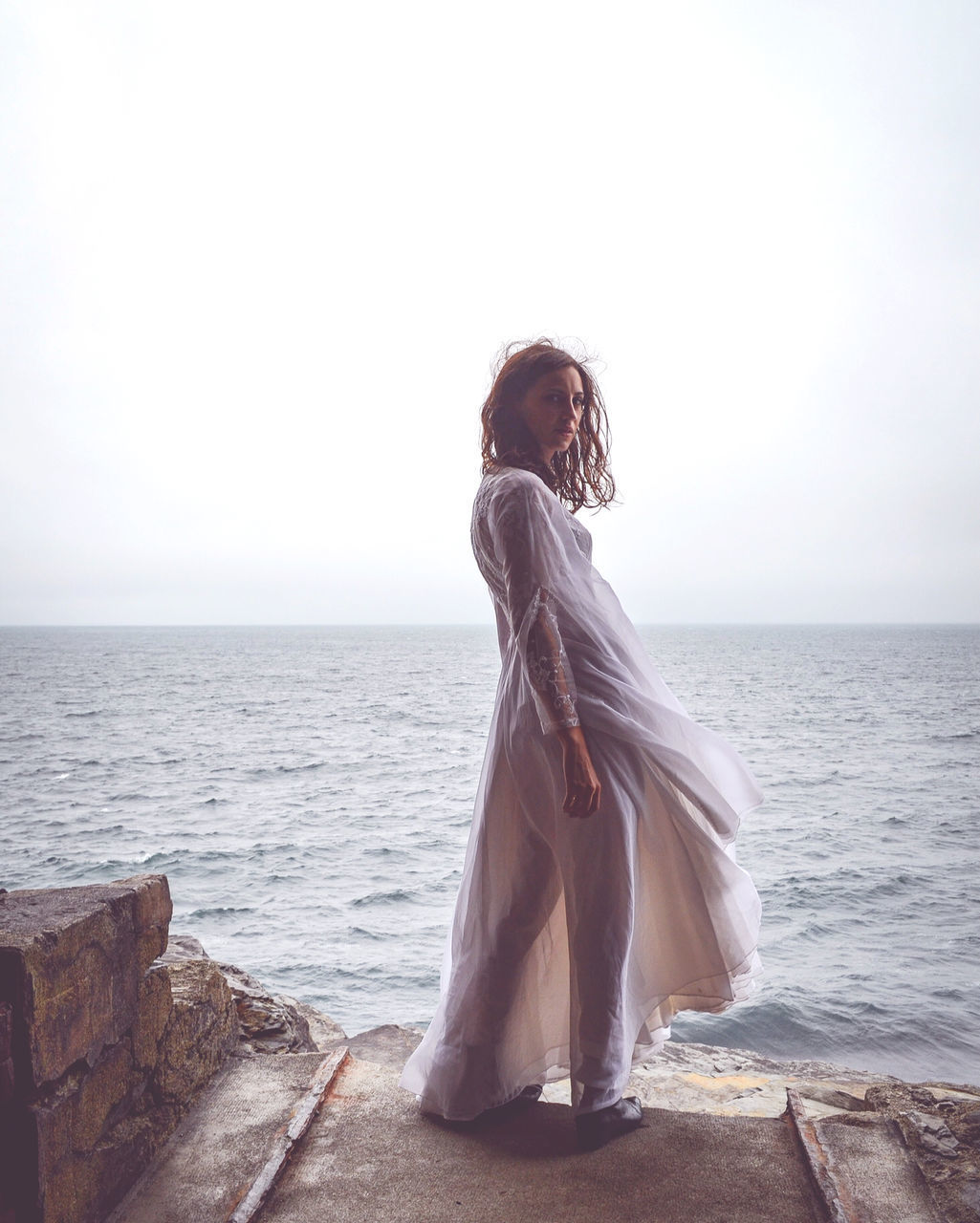 WOMAN STANDING AT SHORE AGAINST SEA