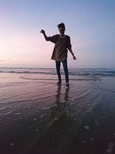 Full length of man standing on beach during sunset