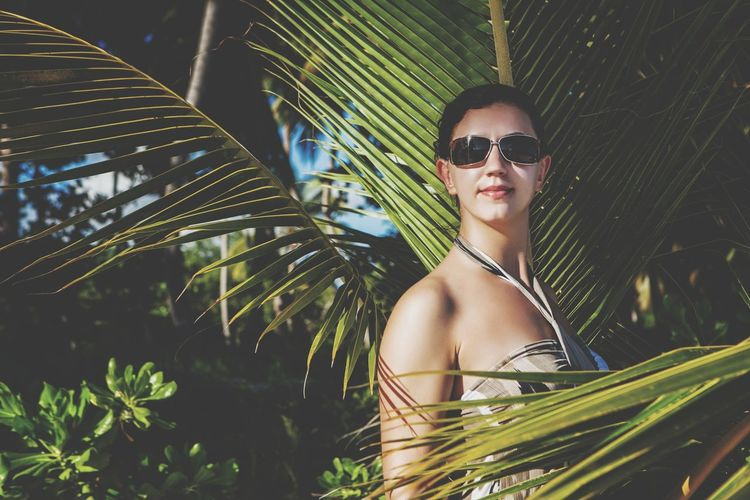 Woman in sunglasses standing by coconut palm tree