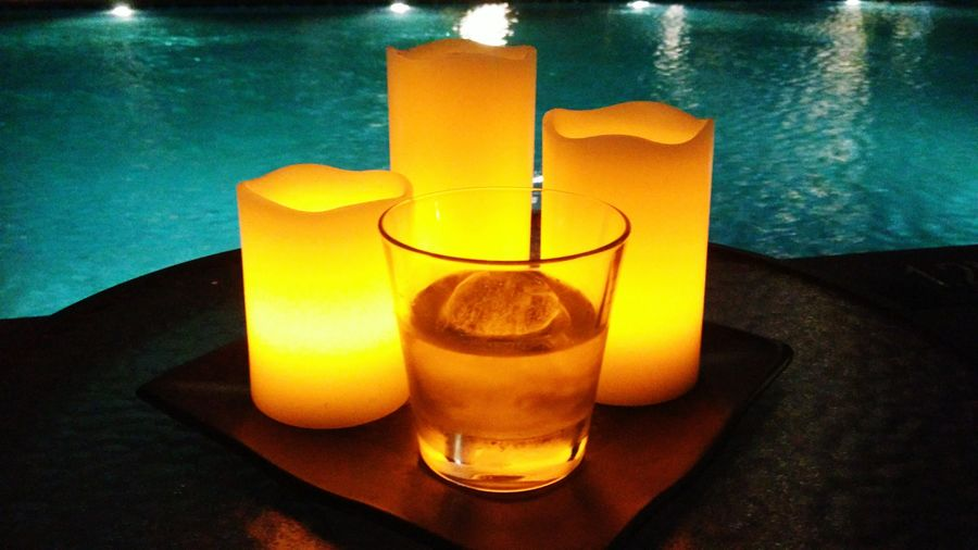 Whiskey and candles next to pool. Warm And Cold Color  Chilling Enjoying Life Booze whisky LED Candle Wax Nightshot Exterior Setting