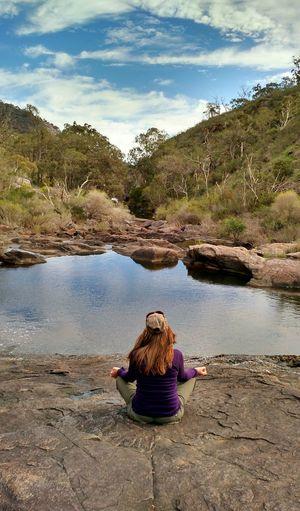 A woman meditates on a rock ledge, above a stream. Environmental Landscape Meditation Meditation Spot Tranquility Tranquil Scene Nature Stream Meditative