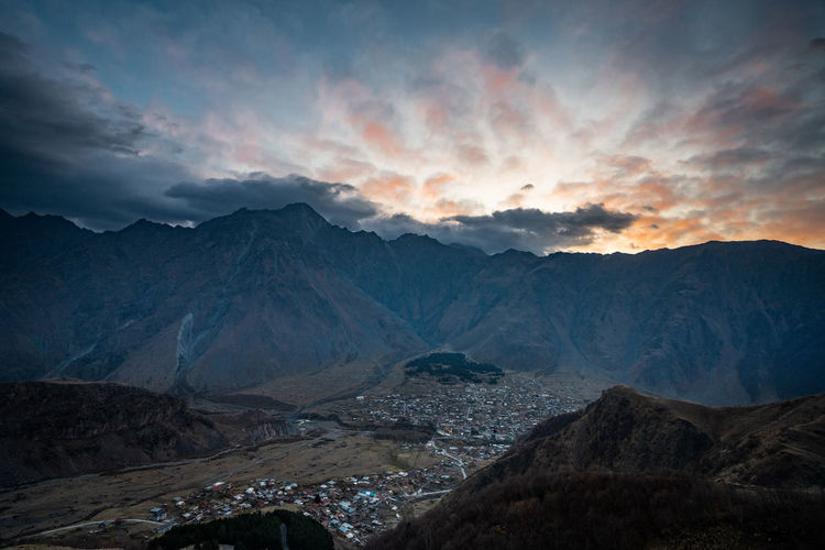 Scenic view of mountains against cloudy sky during sunset