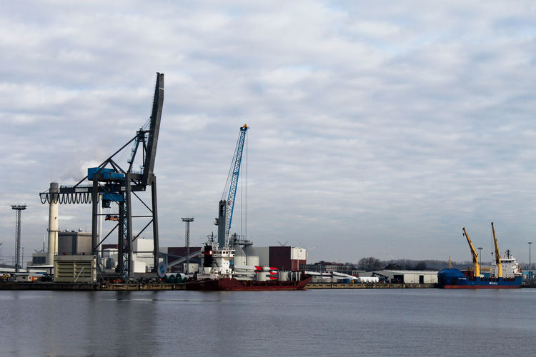Cranes at commercial dock by river against cloudy sky