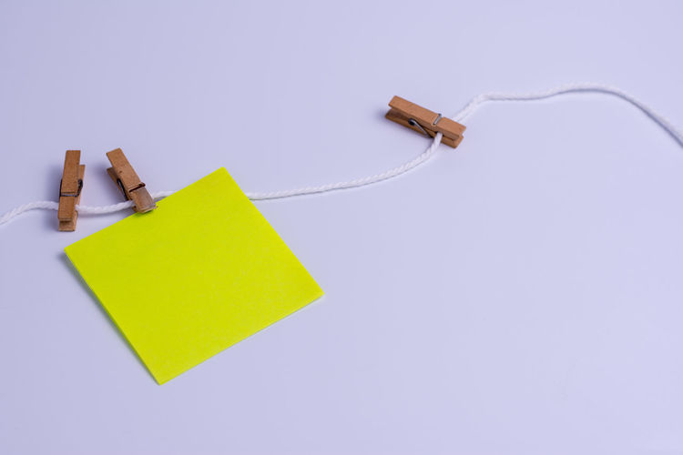 Close up wood paper clip for hanging notes. Adhesive Note Attached Blank Blue Cable Close-up Clothespin Communication Connection Copy Space Cut Out Indoors  Message No People Note Paper Purple Reminder Still Life Studio Shot Technology White Background Yellow