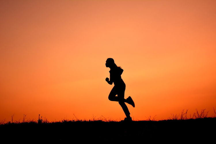 Silhouette Of Woman Running On Field At Sunset