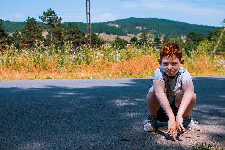 Portrait of boy sitting on road