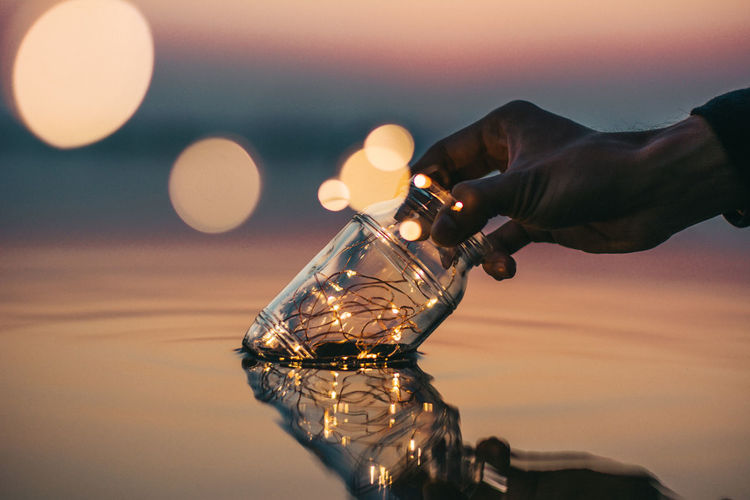 Cropped image of hand putting glass jar in sea during sunset