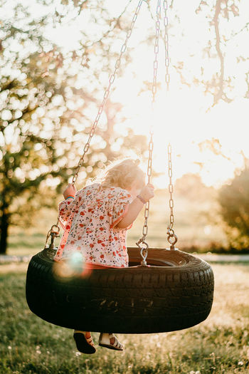 Rear view of girl sitting on tire swing in park