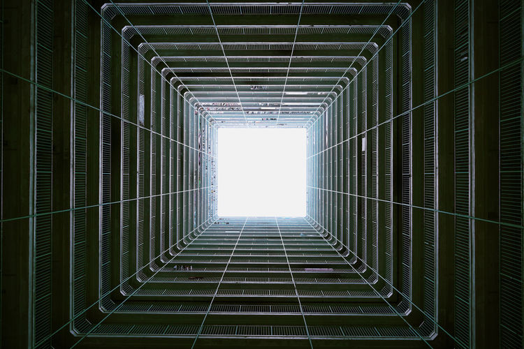 Directly below shot of skylight in building against clear sky