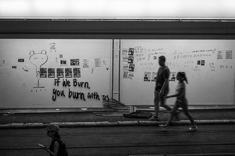 Rear view of people walking on wall