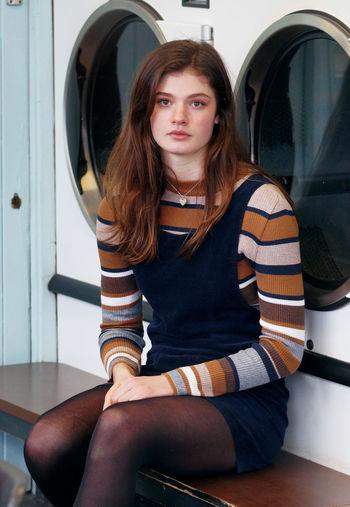 Portrait of beautiful young woman sitting against washing machine