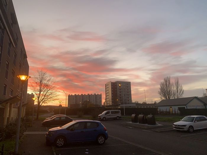 Cars parked on road by buildings against sky during sunset
