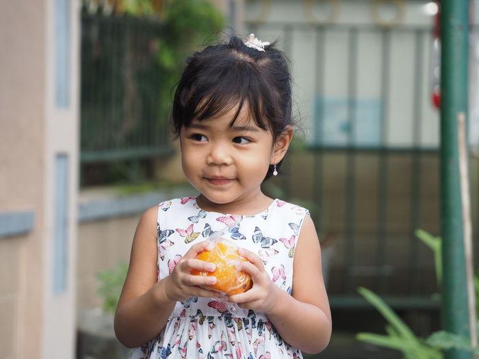 A beautiful asian kid girl wearing butterflies dress smiling while holding an orange fruit