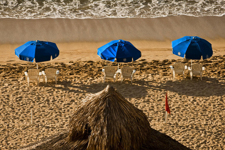 Beach Blue Chairs Day Nature No People Outdoors Red Flag Sand Sea Sunlight Texture Three Umbrellas