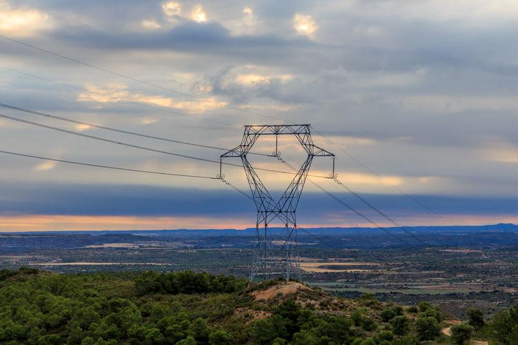 Electricity pylon on landscape against sky during sunset