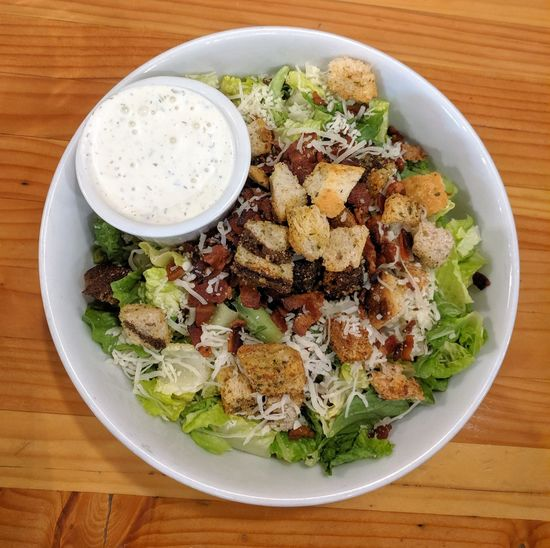 Salad with croutons, bacon, cheese, and ranch dressing