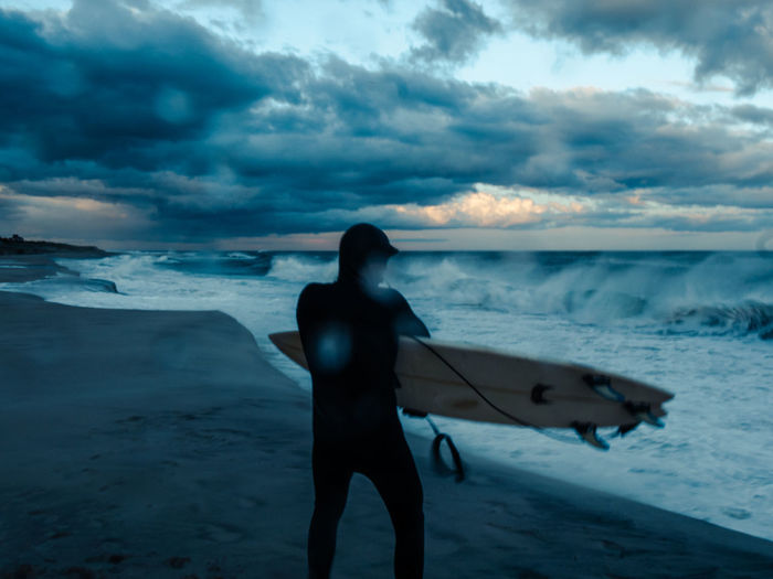 Rear view of man with surfboard standing on shore at beach