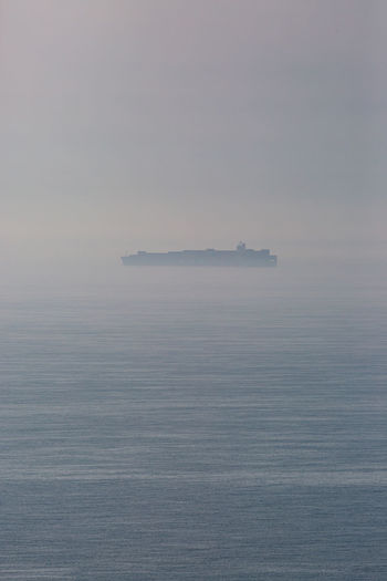 An atmospheric view out to sea with a silhouetted ship on the horizon