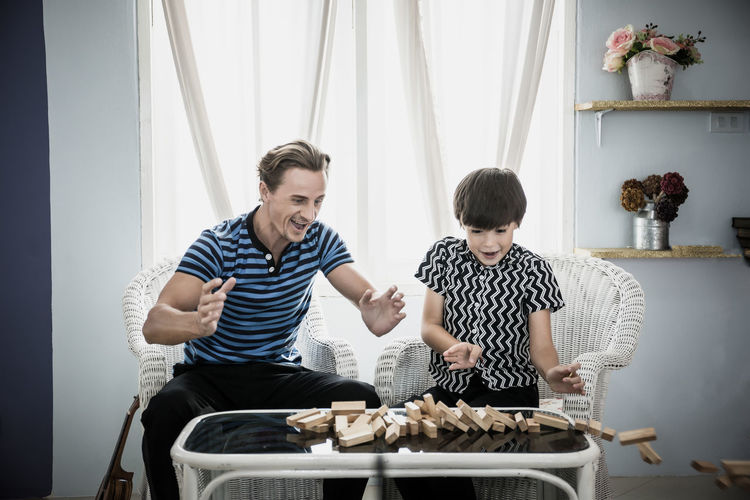 Father and son with toy blocks collapsing on table at home