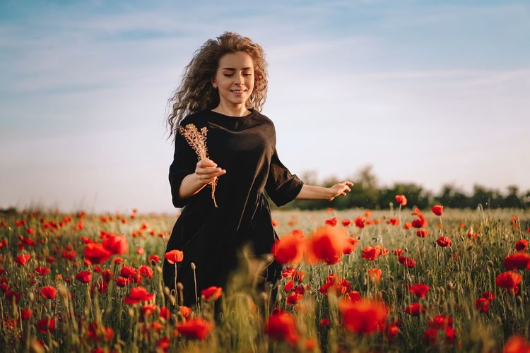 Young woman running in red poppy flowers on field against sky in summer