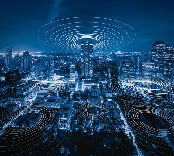 Digital composite image of icons with modern buildings in city at night