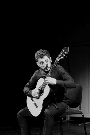 Musical Instrument Music Guitar String Instrument One Person Musician Arts Culture And Entertainment Playing Musical Equipment Front View Sitting Performance Men Holding Real People Artist Skill  Three Quarter Length Stage Plucking An Instrument Electric Guitar Black Background Entertainment Occupation