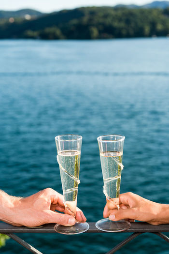 Close-up of couple hands holding champagne on railing by sea