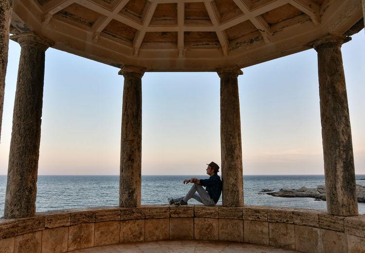 Side view of man sitting in gazebo against sea