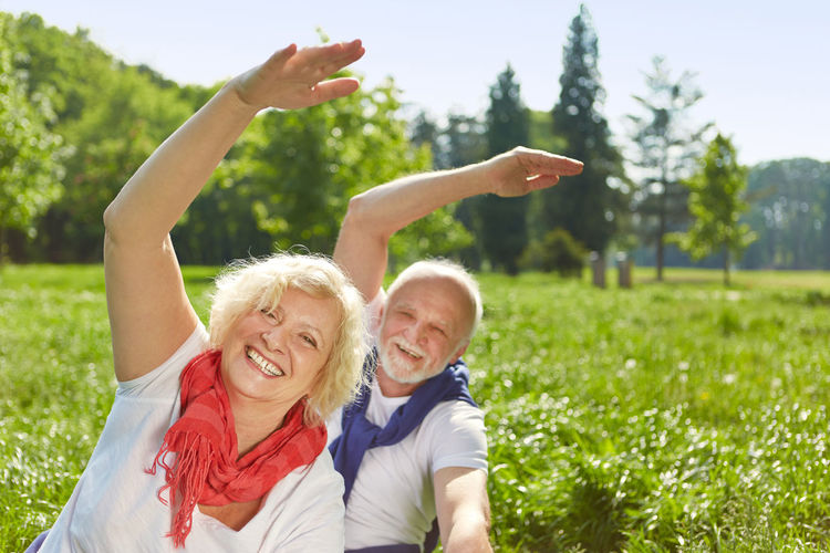Portrait Of Smiling Couple Exercising On Field