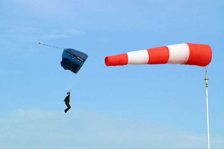 Low angle view of man paragliding by windsock against blue sky