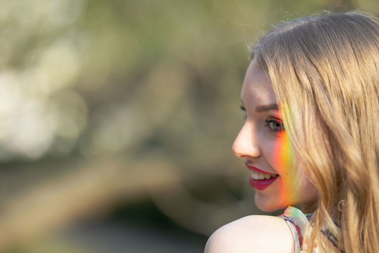 Close-up of young woman with spectrum on face