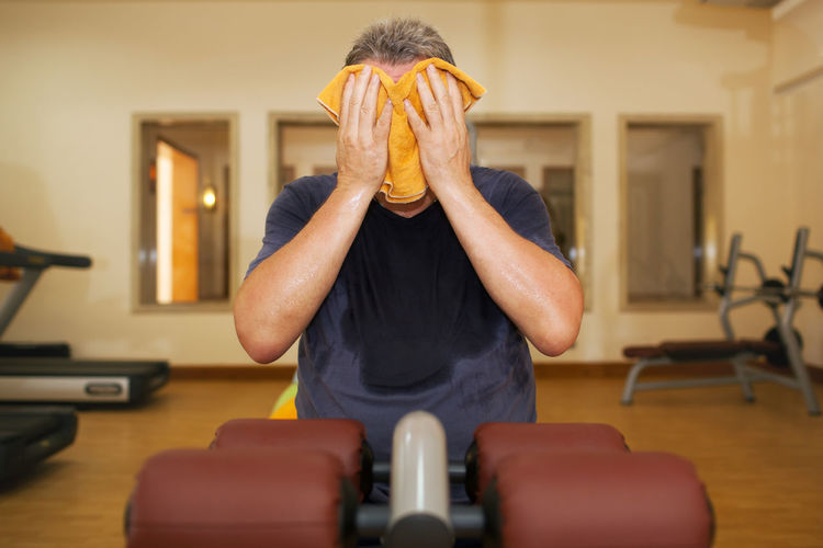 Man wiping face with towel while sitting in gym