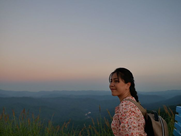 Woman smiling against sky during sunset