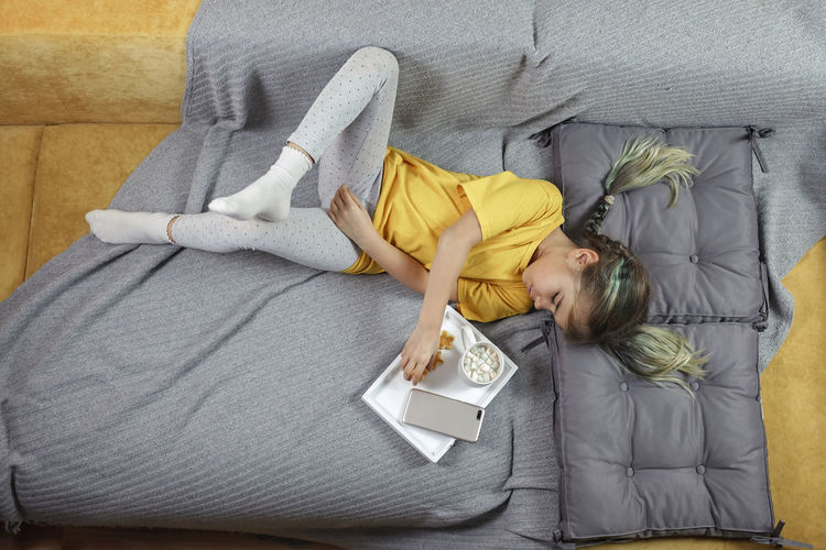 High angle view of girl lying on bed at home