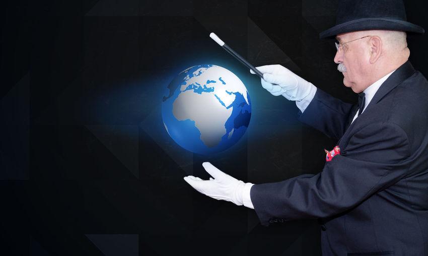 Senior Man Holding Illuminated Globe