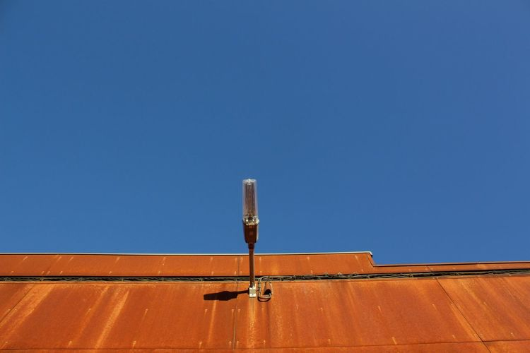 Low angle view of lighting equipment on building against clear blue sky