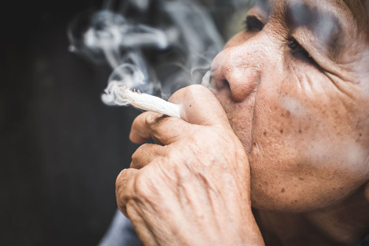 Close-Up Of Senior Woman Smoking Cigarette