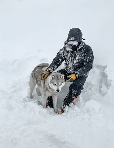 High angle view of man with dog sitting on snow covered land