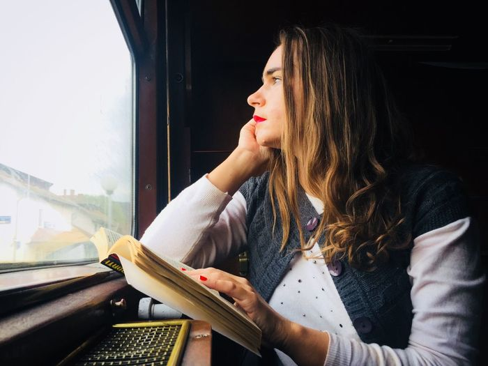 Woman in train sitting next to the window and looking outside with a book in her hand One Person Transportation Train - Vehicle Young Adult Mode Of Transport Window Young Women Indoors  Real People Day Close-up People Adult Adults Only Train Window Fog Autumn Woman Looking Through The Window Thinking Book Read Connected By Travel Fresh On Market 2017