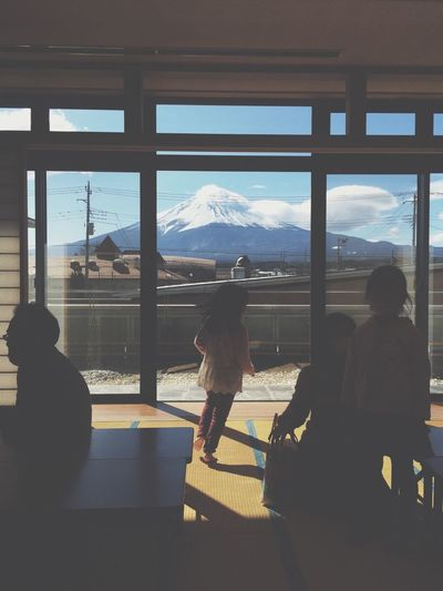 People in building by window against mt fuji