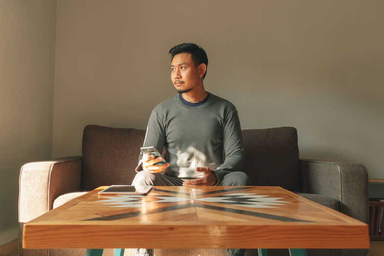 Man looking at camera while sitting on table