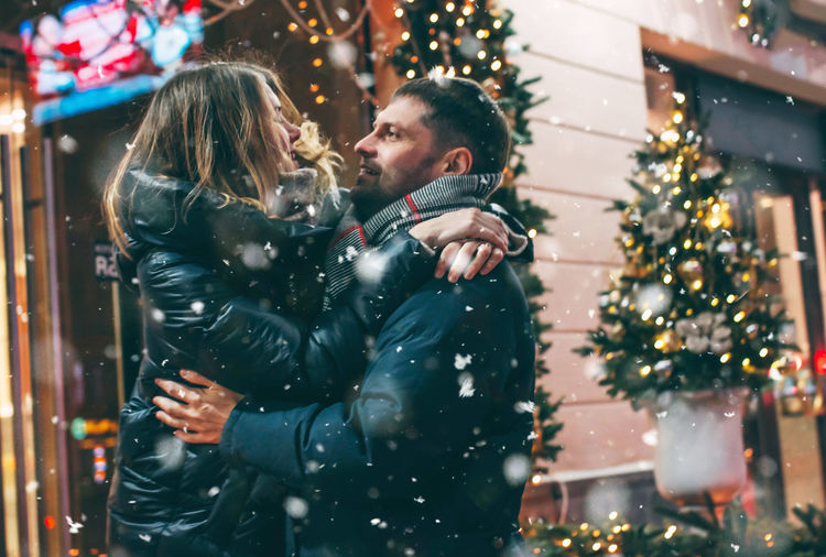 Couple Romancing While Standing Against Buildings At Night During Winter In City