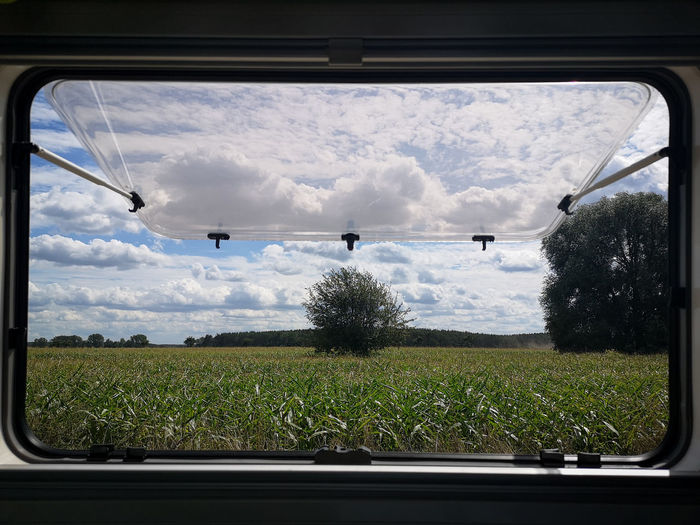 Scenic view of field seen through car window