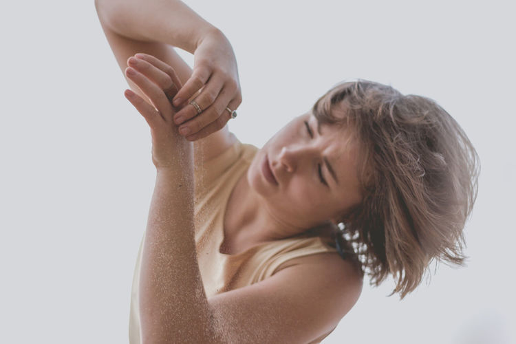 Woman Spilling Sand On Hand Against White Background