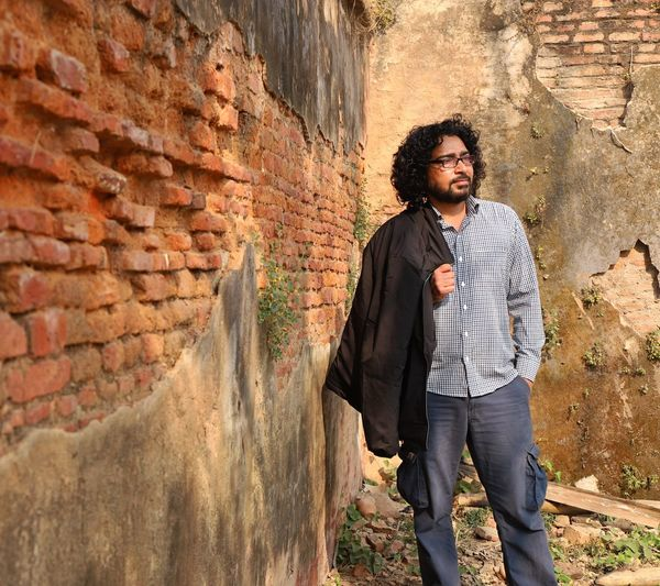 indian yoga instructor in indian culture One Person Young Adult Wall Standing Young Men Front View Three Quarter Length Leisure Activity Casual Clothing Architecture Lifestyles Brick Wall Wall - Building Feature Day Real People Looking At Camera Brick Hands In Pockets Leaning Outdoors Stone Wall Yoga Yoga Instructor Indian Indian Culture