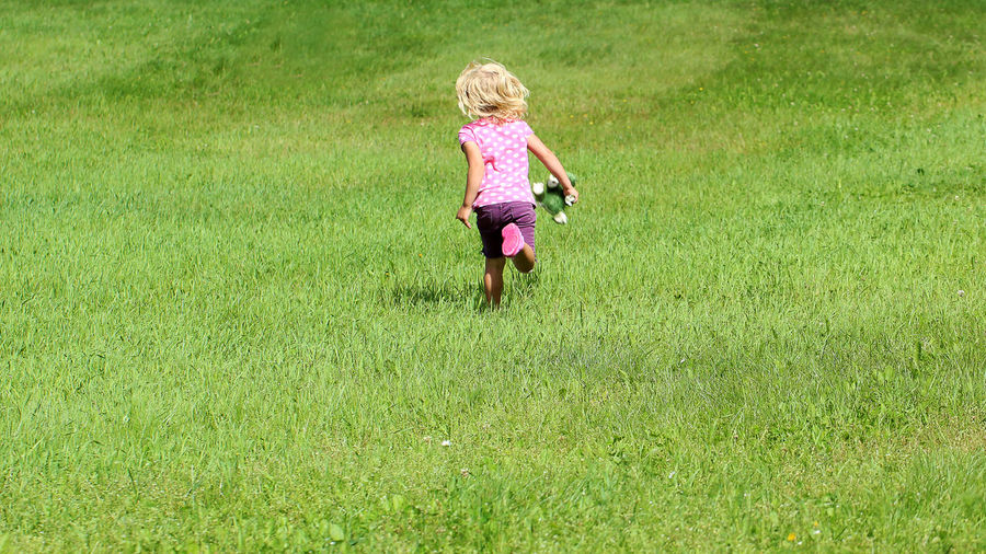 """The little girl runs to her mother and shouts, """"on the way mom"""" Casual Clothing Cudley Toys Day Eyeemphoto EyeEm Gallery Field Full Length Fun Girl Grass Grassy Green Color Growth Kid Kidsphotography Landscape Leisure Activity Lifestyles Nature On The Way Outdoors The Magic Mission Running Human Color Palette Live For The Story Live For The Story"""
