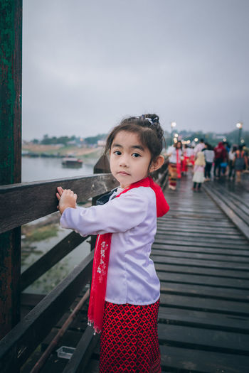 Portrait of cute girl standing by railing against sky