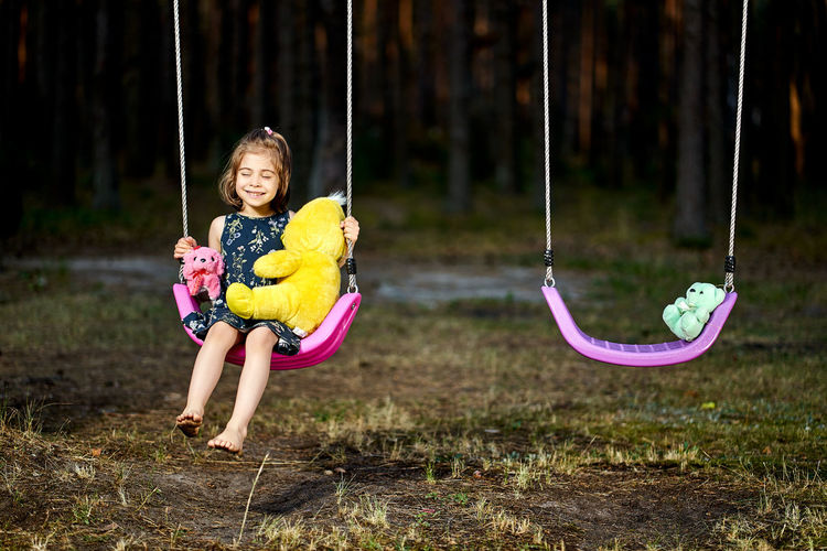 Cute girl sitting on swing at park