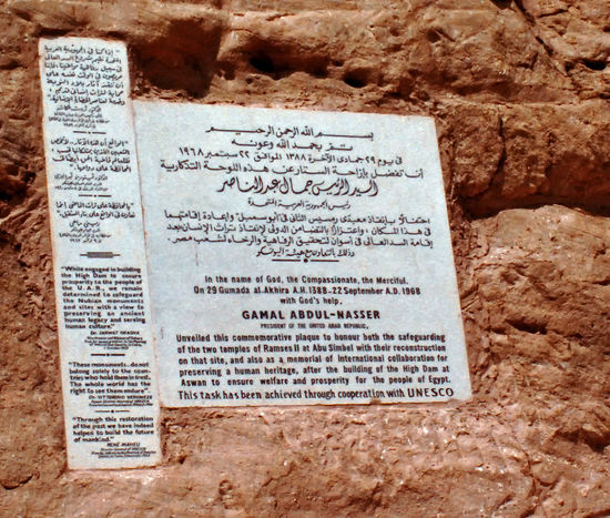 """UNESCO plaque on the Abu Simbel man-made mountain. The Abu Simbel temples are two massive rock temples at Abu Simbel (أبو سمبل in Arabic), a village in Nubia, southern Egypt, near the border with Sudan. They are situated on the western bank of Lake Nasser, about 230 km southwest of Aswan (about 300 km by road). The complex is part of the UNESCO World Heritage Site known as the """"Nubian Monuments"""", which run from Abu Simbel downriver to Philae (near Aswan). The twin temples were originally carved out of the mountainside in the 13th century BC, during the 19th dynasty reign of the Pharaoh Ramesses II. They serve as a lasting monument to the king and his queen Nefertari, and commemorate his victory at the Battle of Kadesh. Their huge external rock relief figures have become iconic. The complex was relocated in its entirety in 1968, on an artificial hill made from a domed structure, high above the Aswan High Dam reservoir. The relocation of the temples was necessary or they would have been submerged during the creation of Lake Nasser, the massive artificial water reservoir formed after the building of the Aswan High Dam on the Nile River. Food Day Paper Text Cookbook Newspaper Close-up Recipe No People UNESCO World Heritage Site Nefertari Aswan, Egypt Abu Simbel Wall Sign Information Medium Abu Simbel And Nefertary Temple. AswanEgypt Ramesis II Arabic And English T Rock Hewn Monuments Focus On The Story"""