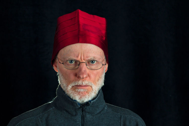 adult man wearing a cummerbund on his head like fez Adult Adults Only Beard Black Background Close-up Cummerbund Eyeglasses  Fez Front View Headshot Indoors  Lifestyles Looking At Camera One Man Only One Person One Senior Man Only Only Men People Portrait Real People Red Senior Adult Standing Studio Shot Waist Sash This Is Aging